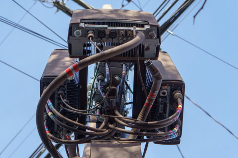 3 Remote Radio Units (size of a large pizza box) as viewed from below. Ugly and unseemly wires don these Remote Radio Units.